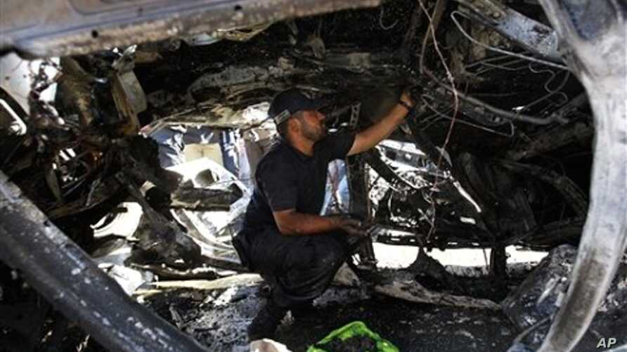 A Palestinian Hamas police officer examines a destroyed car after an explosion in Gaza City, 3 Nov. 2010.