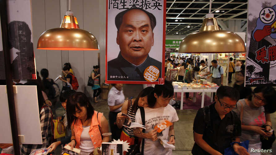 """FILE - Book lovers read beneath poster promoting """"Stange Leung Chun-ying,"""" which depicts the new Hong Kong Chief Executive as the late Chinese leader Mao Zedong, Hong Kong Book Fair, July 18, 2012."""
