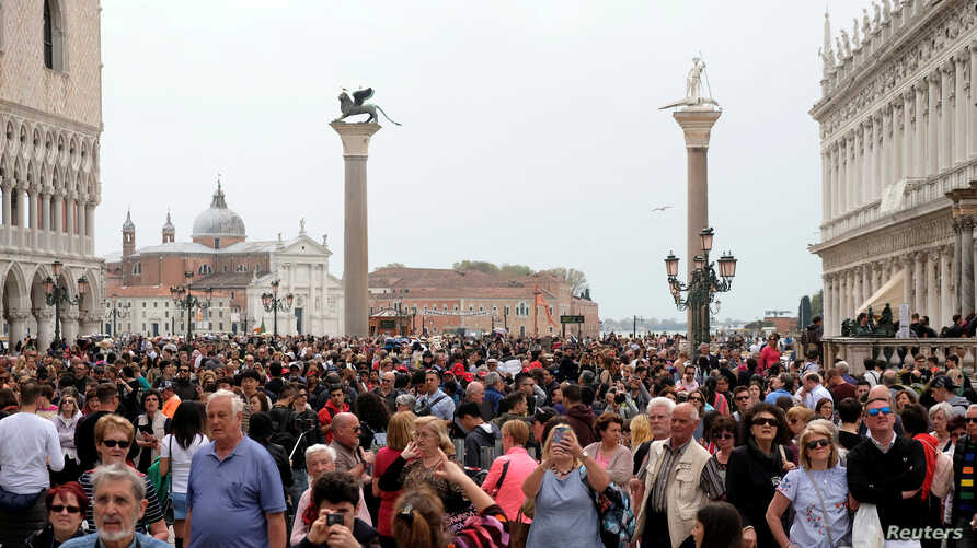 FILE - Tourists are seen at St. Mark's Square in Venice, Italy, April 15, 2018.