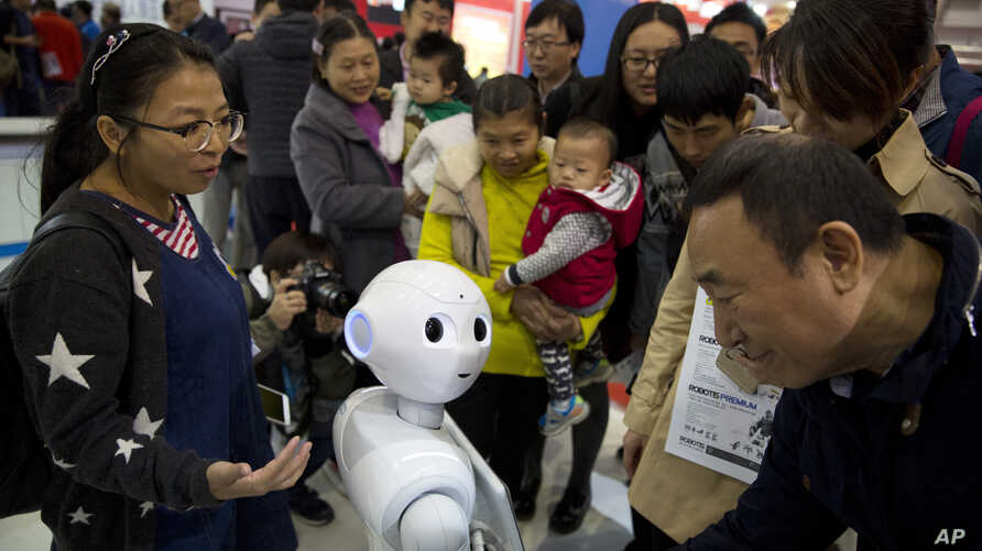 Visitors crowd around Pepper, a companion robot, during the World Robot Conference in Beijing. China, Oct. 21, 2016.