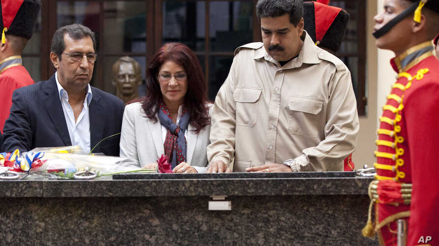 President Nicolas Maduro, right, with Adan Chavez, (left) brother of the late president Hugo Chavez, and Venezuela first lady Cilia Flores, visit the late leader's tomb in Caracas, Venezuela, Nov. 5, 2013.
