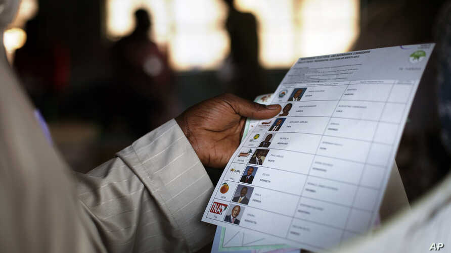 FILE - Kenyan voter holds a presidential ballot at a polling station in the Kibera slum in a general election in Nairobi, Kenya.