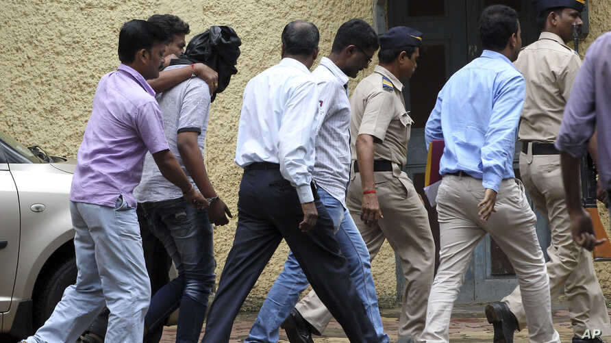 Police officials escort an accused, head covered with black cloth, in the gang rape of a young photojournalist in the Indian financial hub of Mumbai, Aug. 24, 2013.