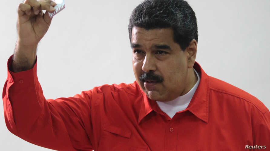 Venezuelan President Nicolas Maduro show his ballot as casts his vote at a polling station during the Constituent Assembly election in Caracas, Venezuela, July 30, 2017.