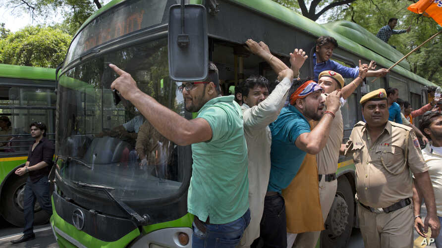 Activists of the youth wing of India's ruling party Bharatiya Janata Party shout slogans as they are detained during a protest against the slaughter of a calf by Congress party's youth wing members, outside the Congress party headquarters in New Delh