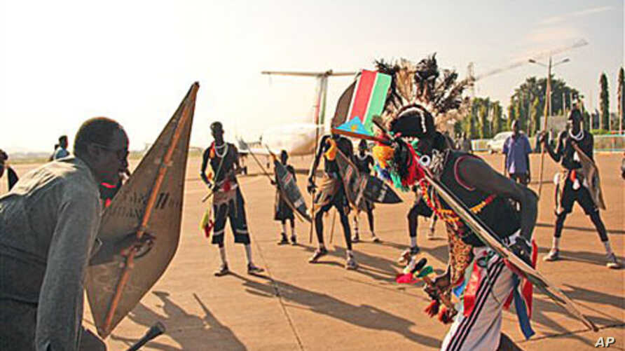 Former militia leader Gabriel Tanginye, left, participates in a traditional dance with dancers from the Nuer tribe at the Juba airport upon his arrival in the southern capital to hold peace talks with the president and army leadership, 14 Oct 2010 (f