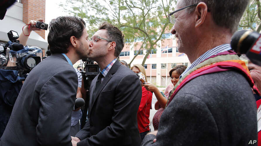 Kevin Patterson, left, and David Larance kiss after exchanging vows, as Rev. John Dorhaer, who performed the ceremony, stands at right, Oct. 17, 2014, in Phoenix, Arizona.