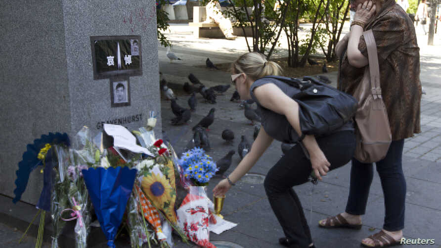 Two women place flowers at a memorial near Concordia University for Lin Jun, a Chinese student who was the victim of a murder and dismemberment, in Montreal June 6, 2012