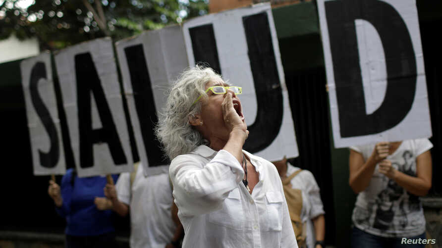 """A woman shouts slogans during a protest outside the World Health Organization (WHO) office in Caracas, Venezuela, Sept. 25, 2017. The letters read """"Health."""""""