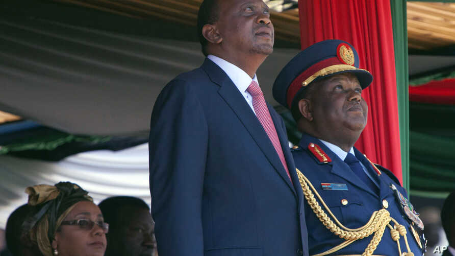 Kenyan president Uhuru Kenyatta, centre, also the Commander-in-Chief of the Armed Forces, left, stands with  Gen Julius Waweru Karangi, right, Chief of the Defence Forces, as they watch the passing out parade and fly over by the Kenyan Air Force, dur