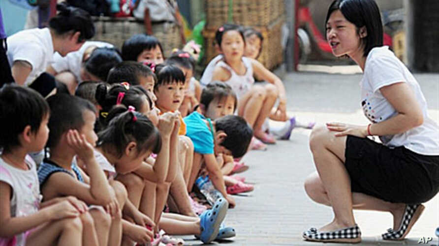 A group of Chinese children, whose migrant parents are unable to afford the kindergarten or pre-school education in China's capital,  gather with volunteers in Beijing, 7 July 2010