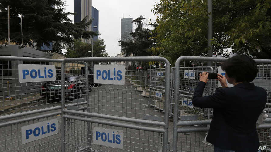 A journalist shoots video behind barriers blocking the road leading to Saudi Arabia's consulate in Istanbul, Oct. 19, 2018.