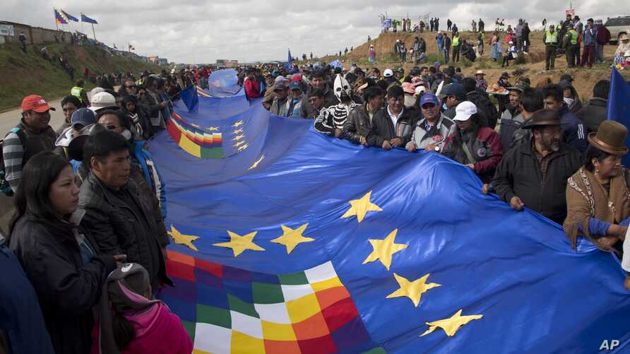 People wave a portion of a giant Bolivian naval flag on the highway between Oruro and La Paz Bolivia, March 10, 2018. A narrow strip of blue stretched for more than 150 miles (nearly 200 kilometers) across the nation Saturday as part of a demonstrati
