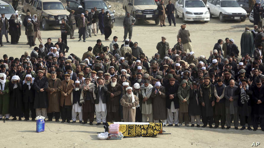 Afghans pray during the funeral of a victim who was killed in Saturday's deadly suicide attack in Kabul, Afghanistan, Jan. 28, 2018.