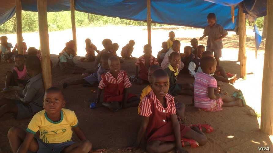Children learn while sitting in sand in a makeshift school at the Chingwizi transit camp, February 2016. (S. Mohfu/VOA)