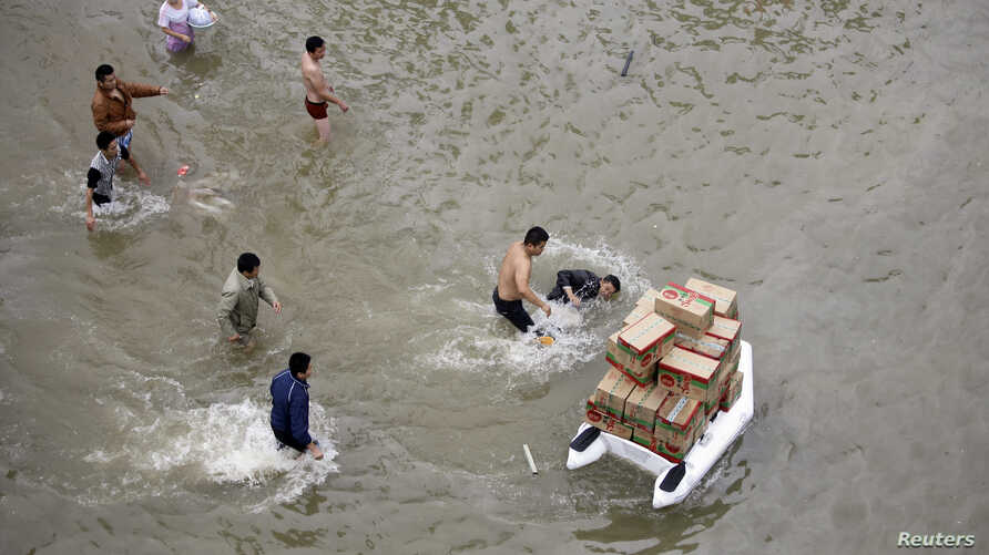 A volunteer (R) transporting boxes of food supplies on an inflatable raft, falls into the water after being pushed by a man (2nd R) as other people look on, on a flooded street during a supply shortage after Typhoon Fitow hit Yuyao October 9, 2013.