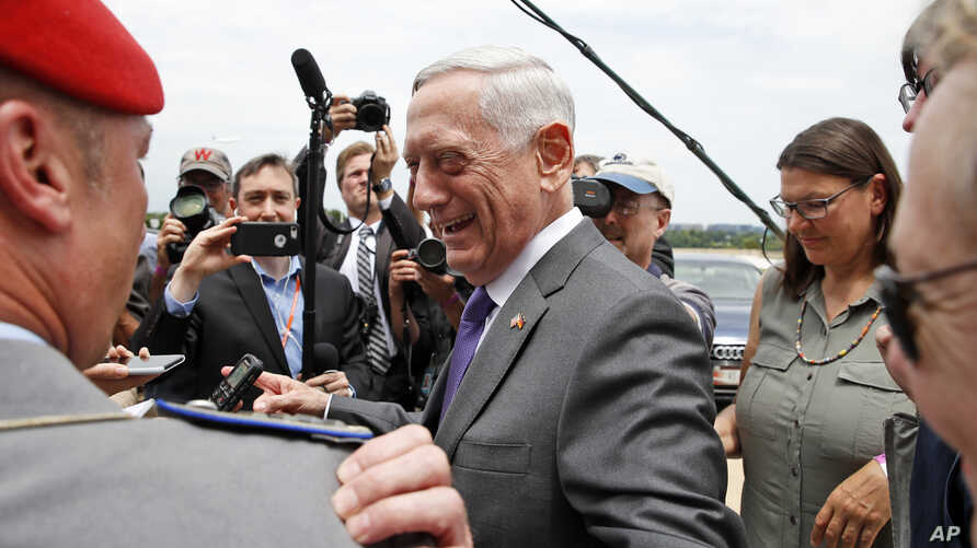 Defense Secretary Jim Mattis smiles at a member of the German army as he speaks with the media at the Pentagon,  June 20, 2018, in Washington.