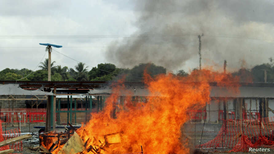 A portion of a Medecins Sans Frontieres (MSF) Ebola treatment unit burns as the MSF begins decommissioning the facility in Monrovia, Liberia, Jan. 26, 2015.