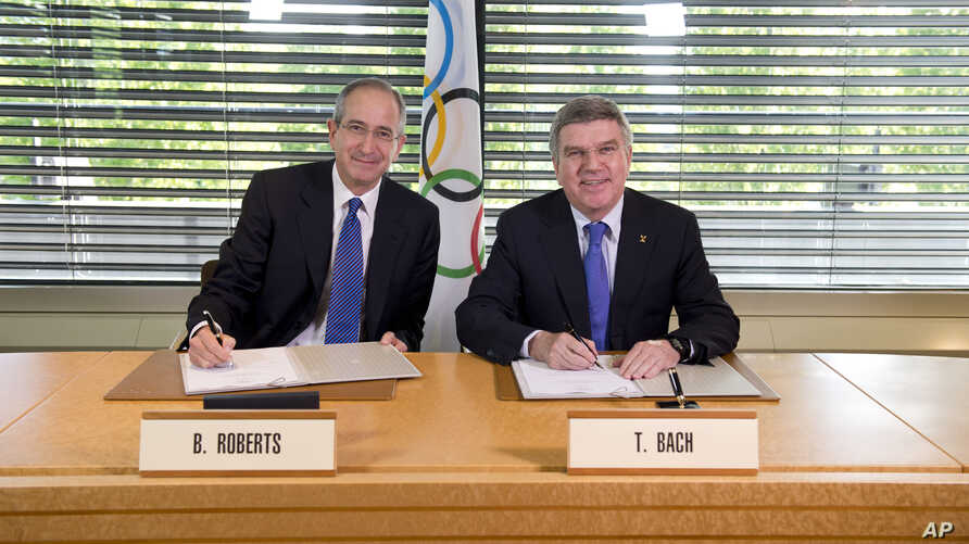 In this photo released by the International Olympic Committee, IOC President Thomas Bach, right, and Chairman and CEO of Comcast Corporation Brian L. Roberts pose for a photograph as they sign an agreement to secure the U.S. broadcast rights to the O