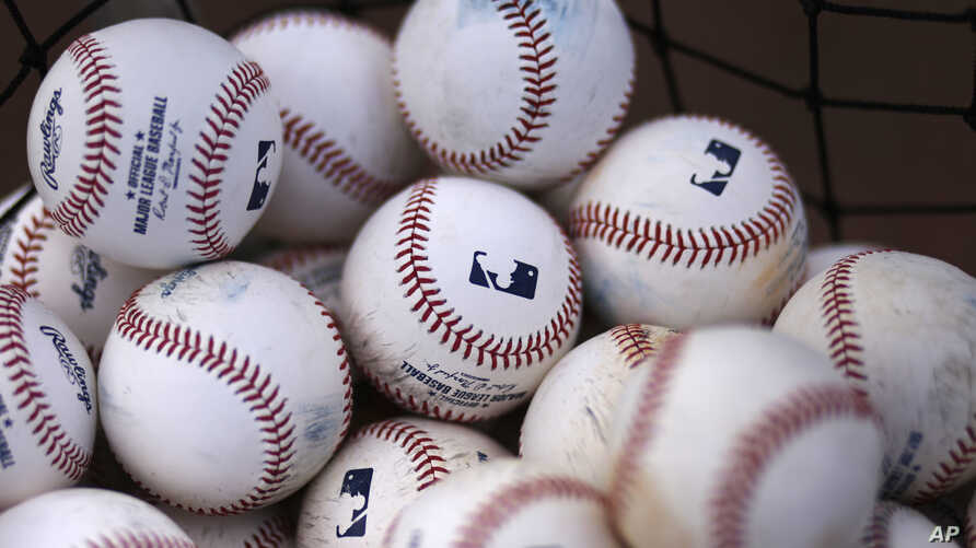 FILE- A basket of baseballs sits on a practice field, Feb. 22, 2015, during a baseball spring training workout in Bradenton, Fla. Facebook is getting deeper into the professional sports streaming game, signing a deal with Major League Baseball to sho