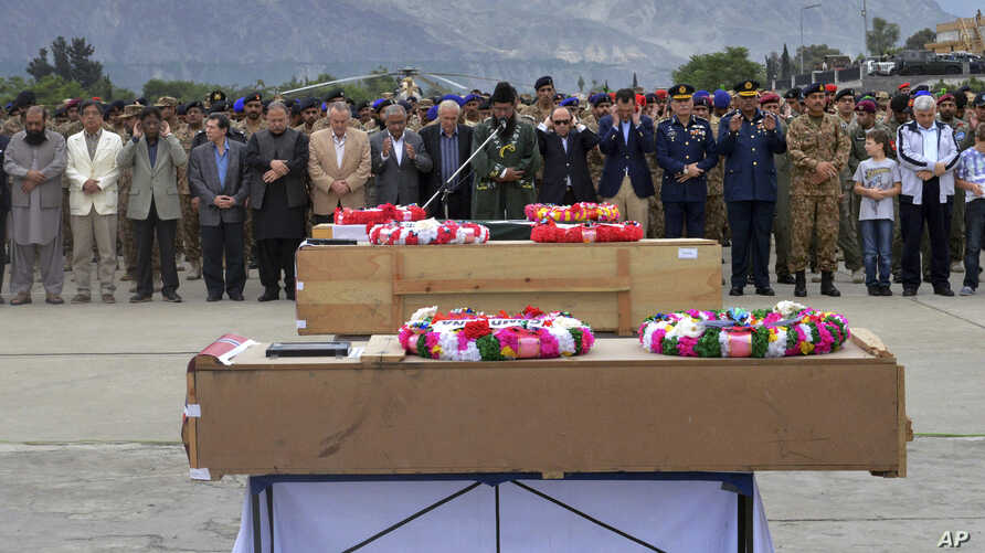 FILE - Pakistani military officials and others offer prayers for victims of a helicopter crash prior to their transport to Islamabad, at the Gilgit airport, in the Gilgit-Baltistan region of Pakistan, May 9, 2015.