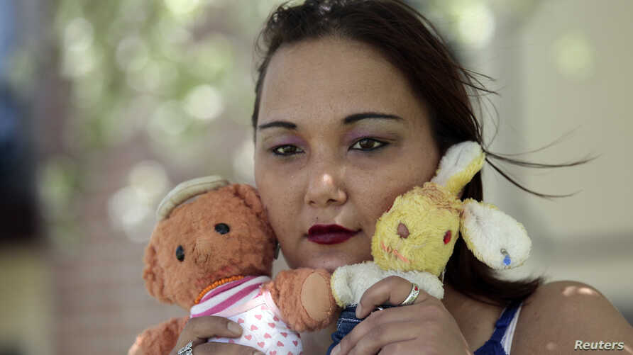 Inga Whatcott, adopted from Russia, holds two stuffed dolls she saved from her orphanage in Russia, outside her apartment in Battle Creek, Michigan, May 2013.