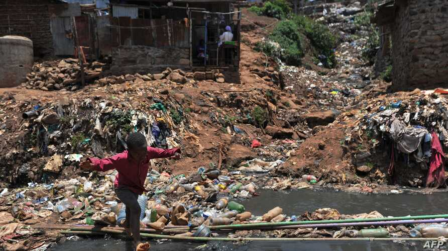 A young resident of Nairobi's Kibera slum, one of Africa's largest slums, crosses a heavily polluted section of the Ngong river on September 19, 2018.