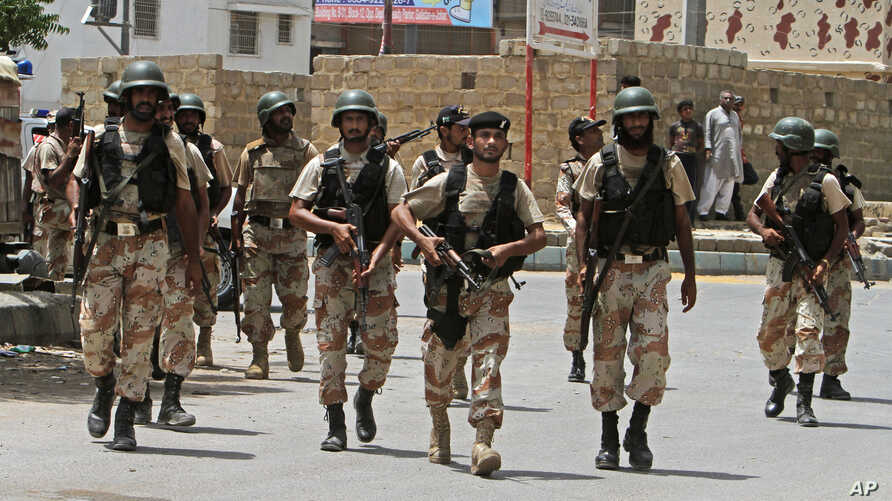 Security personnel inspect the site around a training center after gunmen attacked the facility in Karachi, Pakistan, June 10, 2014.