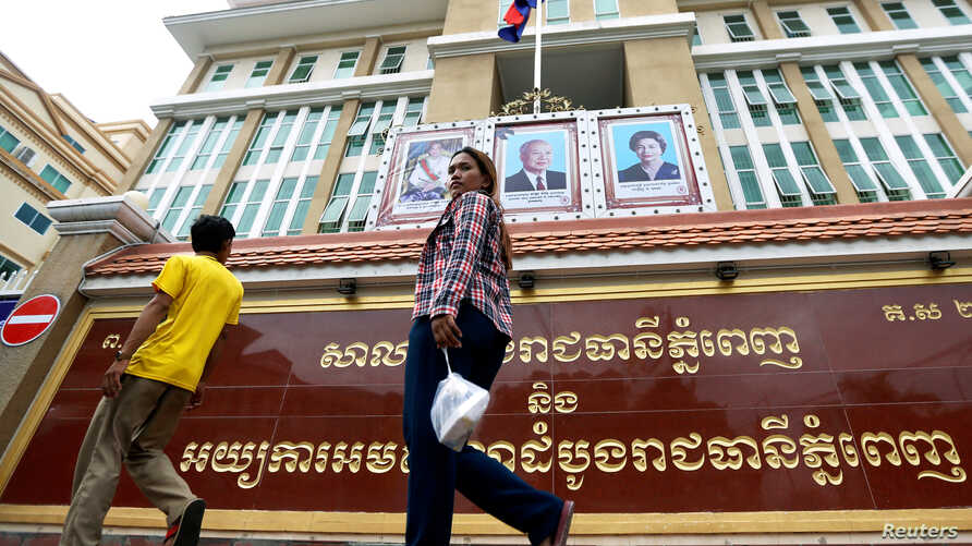 People walk in front of the Phnom Penh Municipal Court before a verdict against six union leaders, in Phnom Penh, Cambodia, Dec. 11, 2018.