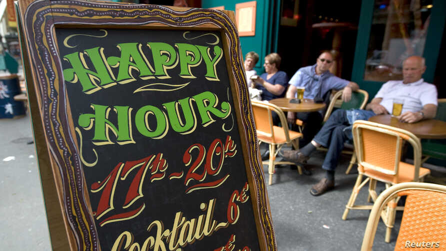 FILE - A happy hour sign is seen in front of a bar on the Grands Boulevards in Paris, France.