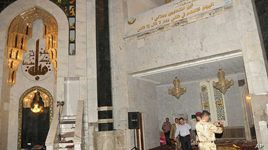 Security personnel inspect the site of a bomb attack inside the Umm al-Qura mosque in Baghdad, August 28, 2011