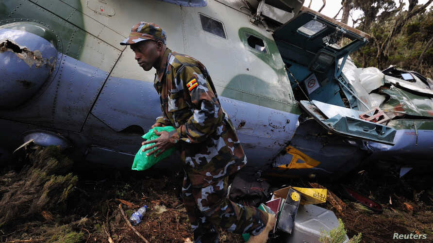 A Uganda People's Defence Air Force (UPAF) crewman walks next to a Somalia-bound Ugandan Mi-24 attack helicopter that crashed at Mount Kenya, August 13, 2012.
