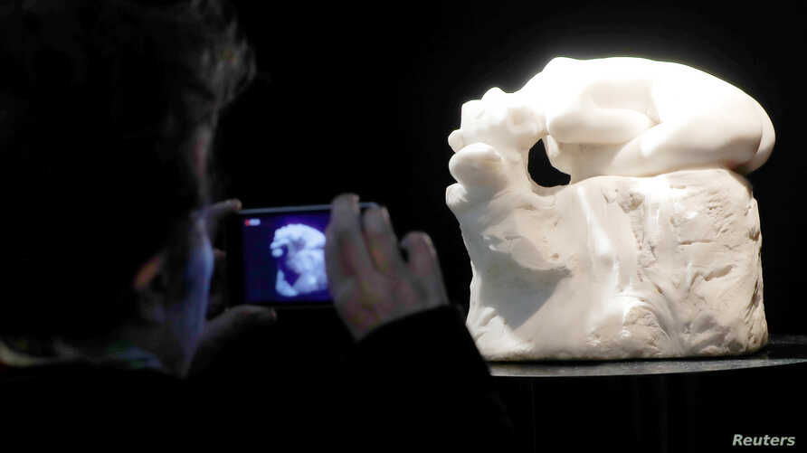 """A visitor looks at """"Andromede,"""" a marble by French sculptor Auguste Rodin (1840-1917) displayed at the auction house Artcurial in Paris, France, March 17, 2017."""