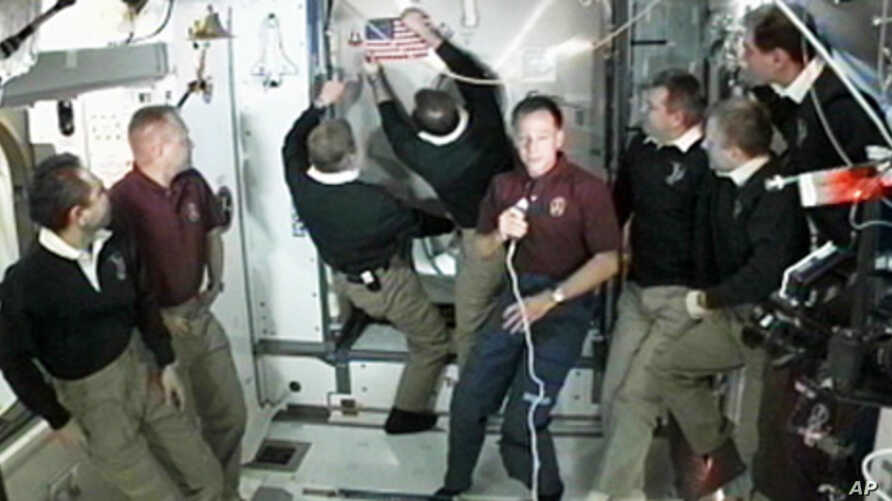 The members of the STS-135 and Expedition 28 crews participate in a farewell ceremony aboard the International Space Station in preparation for the closure of hatches between the orbital complex and space shuttle Atlantis, Jul 18, 2011
