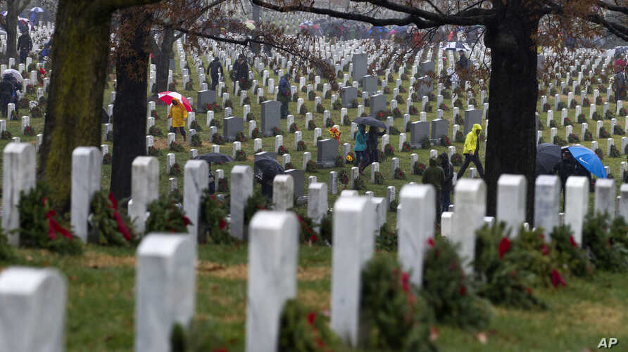 Volunteers help to lay holiday wreaths at graves at Arlington National Cemetery in Arlington, Va., Dec. 15, 2018, during Wreaths Across America Day.