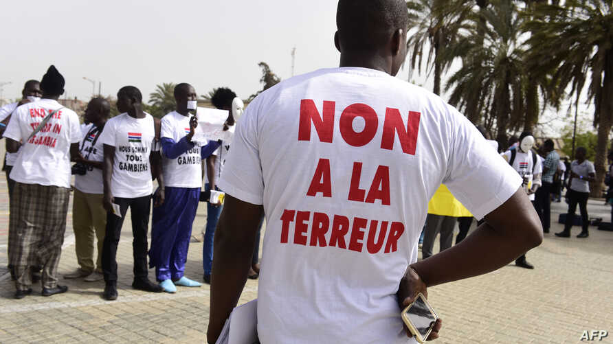 "FILE - People wearing T-shirt reading ""no to terror"" demonstrate in Dakar, April 22, 2016. On Friday, a court in Dakar sentenced more than a dozen suspected militants to prison."