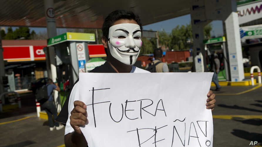 """A masked protester holds a sign that says """"Pena Out!"""" as people angry over hiked gas prices under President Enrique Pena Nieto's government block for hours one of the city's oldest gas stations at main intersection in Mexico City, Jan. 2, 2017."""
