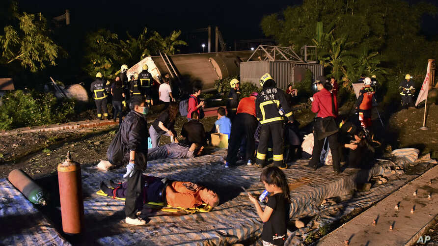 Rescue workers tend to the injured at the site of a train derailment in Yilan county, northeastern Taiwa on Sunday, Oct. 21, 2018.