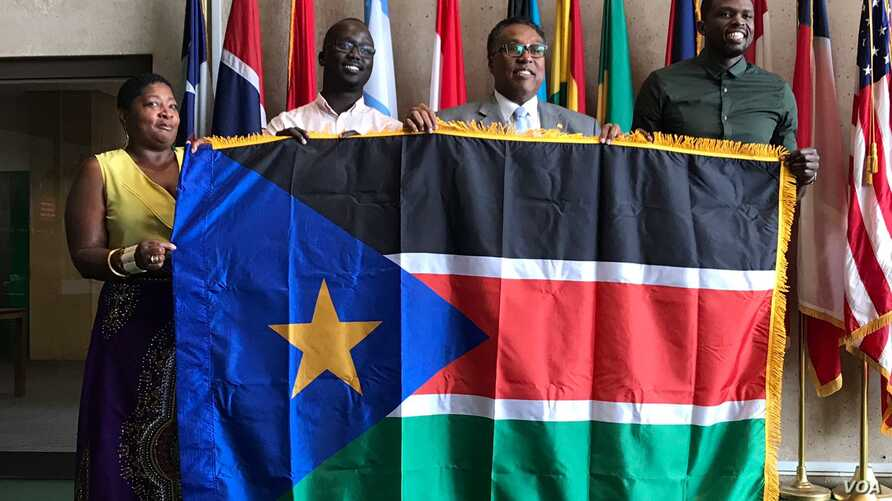 From left, Regina Onyeibe, Africa liaison for Dallas, Dallas-area resident Michael Majok, Dallas City Councilman Dwaine Caraway and pro basketball star Luol Deng participate in the raising of the South Sudanese flag at City Hall in Dallas, Texas, Jul