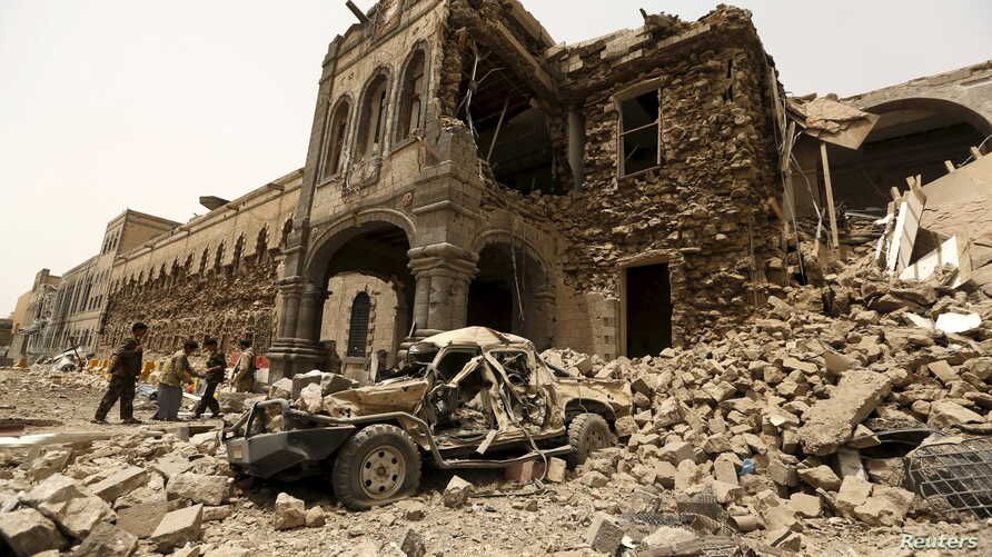 Houthi militants stand in front of the Defense Ministry compound after it was hit by Saudi-led airstrikes in Yemen's capital Sana'a, June 10, 2015.