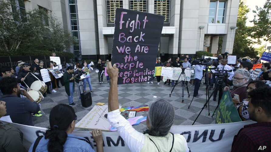 More than 100 protesters demonstrate outside the federal courthouse where a federal judge heard arguments over the U.S. Justice Department's request to block three California laws that extend protections to people in the country illegally, in Sacrame