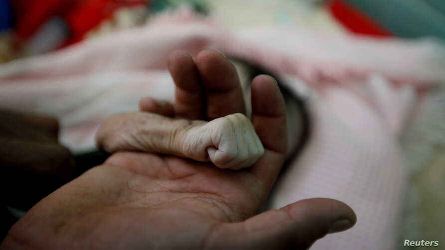 Saleh al-Faqeh holds the hand of his 4-month-old daughter, Hajar, who died at the malnutrition ward of al-Sabeen hospital in Sanaa, Yemen, Nov. 15, 2018.