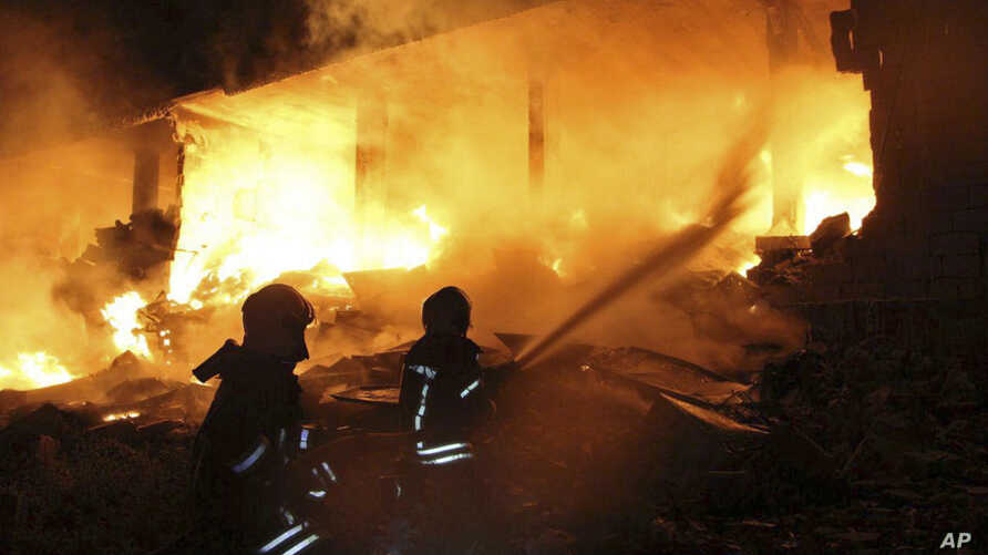 This photo provided by the Syrian Civil Defense White Helmets, which has been authenticated based on its contents and other AP reporting, shows Syrian White Helmet civil defense workers extinguishing a fire at the scene of an explosion that hit a fiv