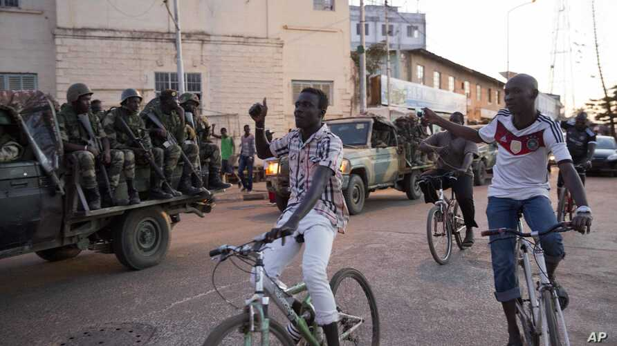 People cheer as ECOWAS Senegalese troops take position near to the state house in the Gambian capital Banjul Sunday Jan. 22, 2017, one day after Gambia's defeated leader Yahya Jammeh went into exile. ECOWAS troops are moving in to prepare for the ret