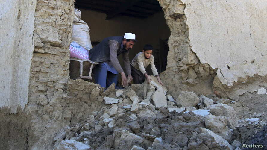 A man and his son clear the rubbles from their house after it was damaged by an earthquake in Behsud district of Nangarhar Province, Afghanistan, Oct. 27, 2015.