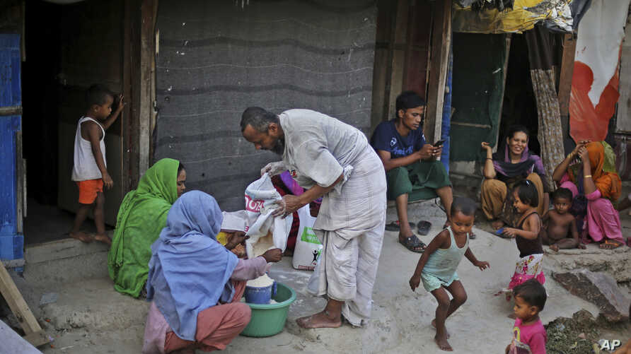 A Rohingya refugee distributes wheat, donated by locals, among other refugees at a camp for the refugees in New Delhi, India.