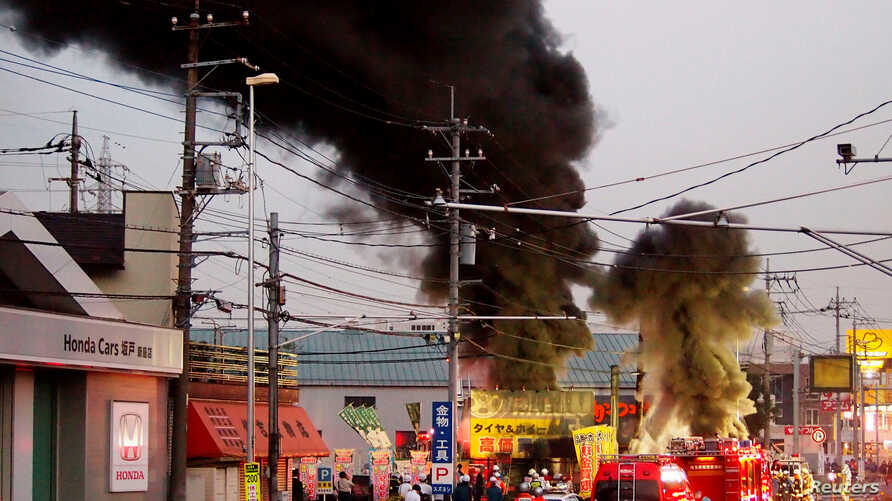 Firefighters gather around black smoke spewing from an unmanned underground cable facility in Niiza, Saitama prefecture on October 12, 2016. TEPCO said smoke was detected at its unmanned power substation in Niiza city, near Tokyo, and officials are l