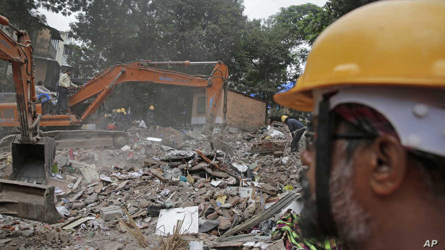 Rescuers look for survivors on the second day after a five-story building collapsed in the Ghatkopar area of Mumbai, India, July 26, 2017.