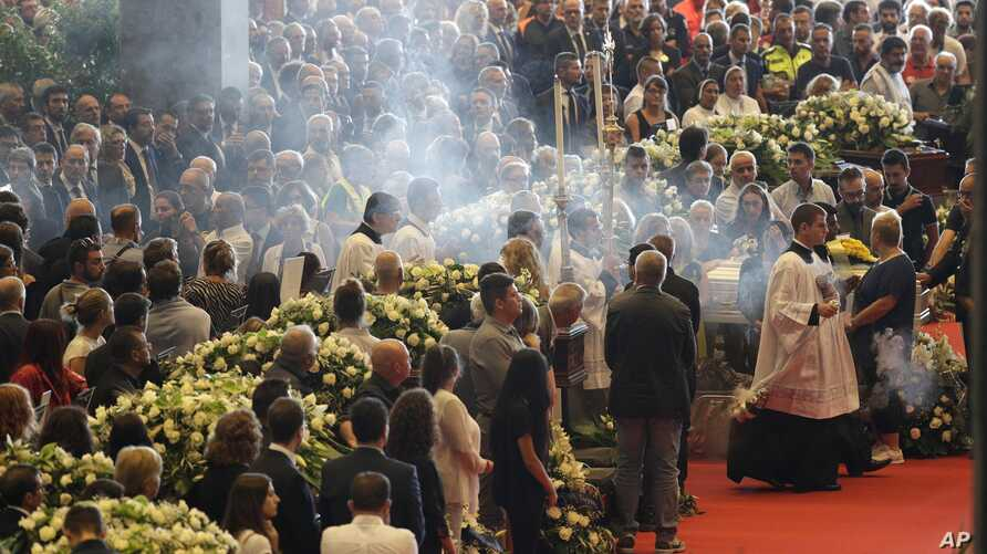 Incense is spread during a funeral service for some of the victims of a collapsed highway bridge, in Genoa's exhibition center Fiera di Genova, Italy, Saturday, Aug. 18, 2018.