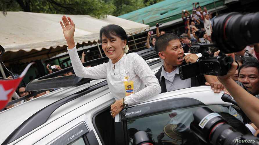 Aung San Suu Kyi waves to people who have gathered to meet her at the Mae La refugee camp, where tens of thousands of her compatriots live, near Mae Sot at the Thai-Burmese border June 2, 2012.